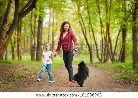 Mother and child walking in forest and playing with dog - stock photo