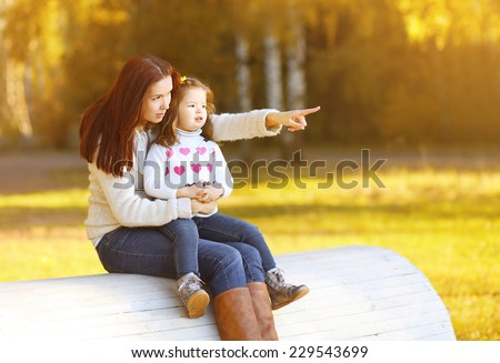Mother and child walking on autumn day enjoying warm weather - stock photo