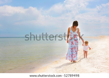 mother and child walking on beach - stock photo
