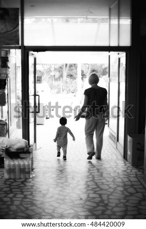 Mother and child walking towards exit door, monochrome image