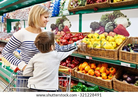 Mother and child with bell pepper in vegetables department in the supermarket