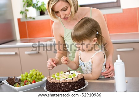 Mother and child with chocolate cake in modern kitchen