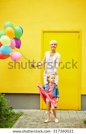 mother and child with colorful balloons on a yellow background
