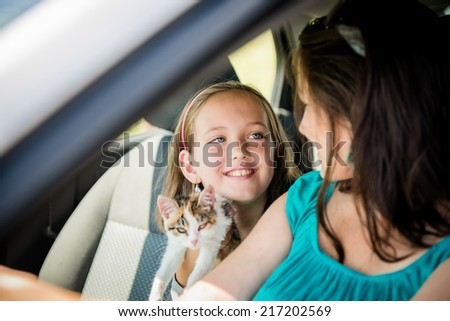 Mother and child with kitten having fun in car - stock photo