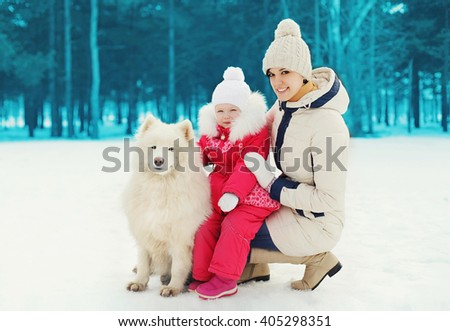Mother and child with white Samoyed dog in winter day - stock photo