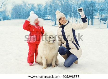 Mother and child with white Samoyed dog makes selfie portrait on smartphone in winter day - stock photo