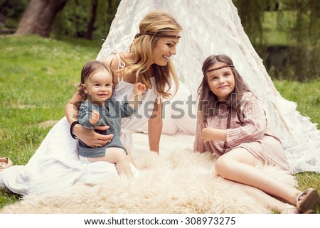 Mother and children are sitting in a tent tee pee and having fun with a nature - stock photo
