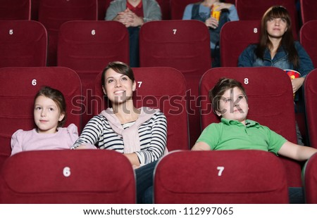 Mother and children are watching movie - stock photo