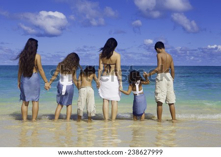 mother and children at the beach - stock photo