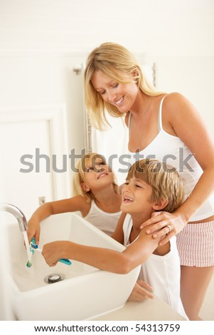 Mother And Children Brushing Teeth In Bathroom Together