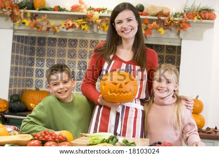 Mother and children carving pumpkins - stock photo