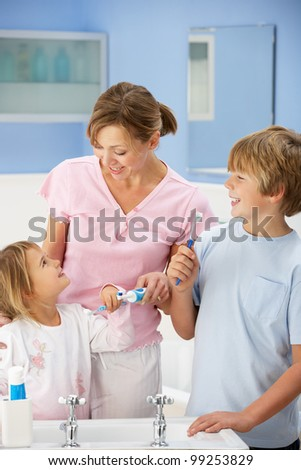 Mother and children cleaning teeth in bathroom - stock photo