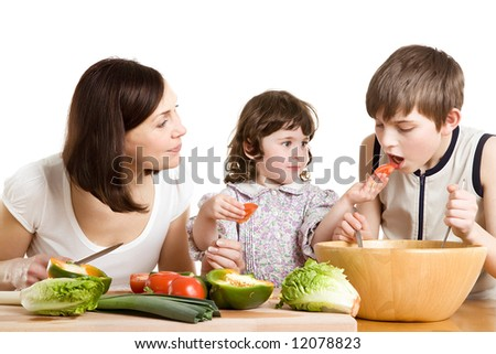 mother and children cooking salad at the kitchen - stock photo