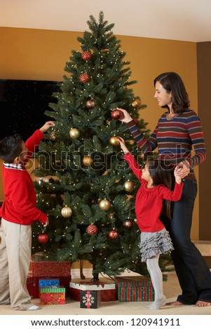 Mother And Children Decorating Christmas Tree - stock photo