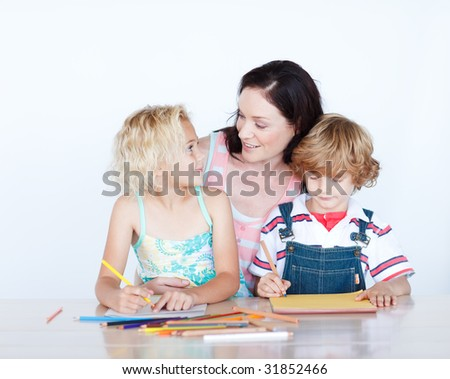 Mother and children doing homework together at home - stock photo