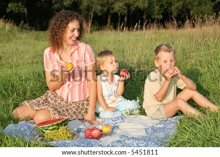 mother and children eat fruits sitting on the grass