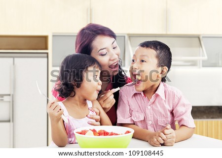 Mother and children eating healthy snack - fruit salad. Shot in the kitchen - stock photo