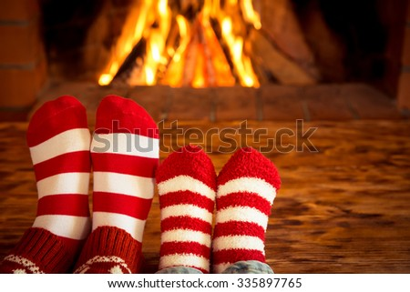 Mother and children feet in Christmas socks near fireplace. People relaxing at home. Winter holiday concept - stock photo