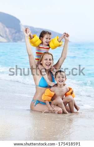 Mother and children having fun on the beach