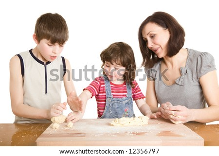 mother and children in the kitchen making a dough - stock photo