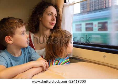 mother and children  look in train`s window - stock photo