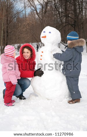 mother and children make snowman - stock photo