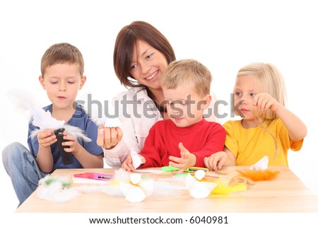 mother and children making angels from paper and feather