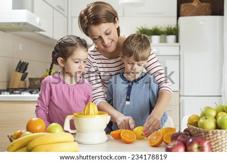 Mother and children making fresh juice - stock photo