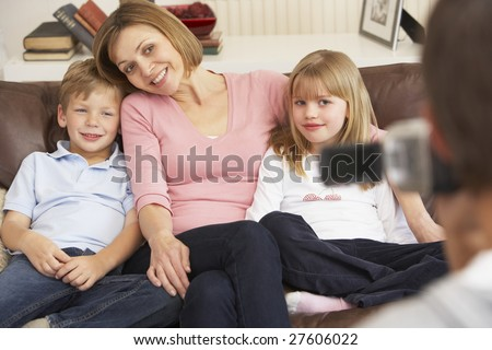 Mother And Children On Sofa Being Filmed On Video Camera