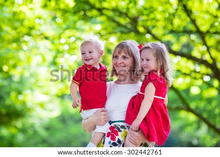 Mother and children play in a park. Woman holding little toddler daughter and son. Siblings with little age difference. Boy and girl twins. Young grandmother with grandchildren in sunny summer garden. - stock photo