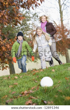 Mother and children playing football in autumn garden