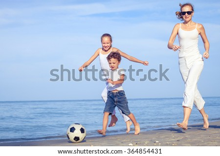 Mother and children playing on the beach at the day time. Concept of friendly family. - stock photo