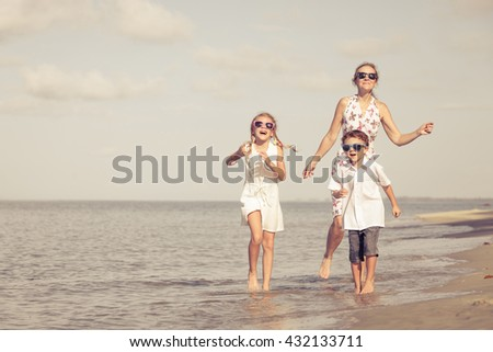 Mother and children playing on the beach at the day time. Concept of friendly family.