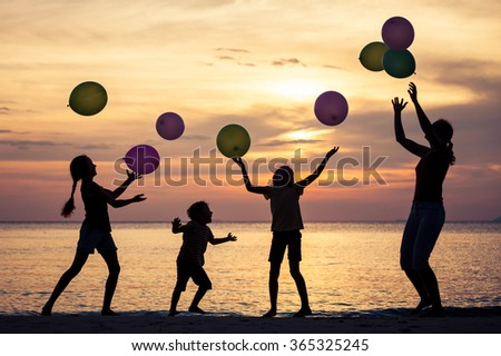 Mother and children playing on the beach at the sunset time. Concept of friendly family. - stock photo