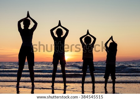Mother and children playing on the beach at the sunset time. Concept of happy friendly family. - stock photo