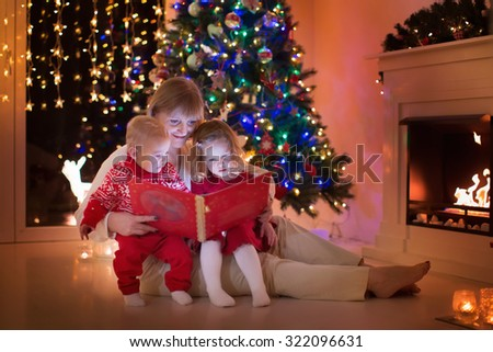 Mother and children read a book at fireplace on Christmas eve. Family with child celebrating Xmas. Decorated living room with tree, fire place and candles. Winter evening at home for parents and kids. - stock photo