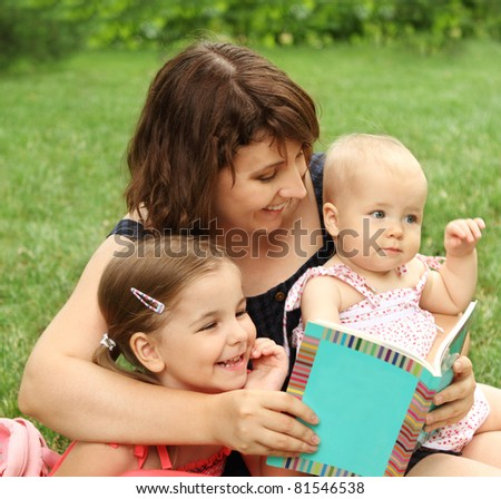 Mother and children reading a book in summer park - stock photo
