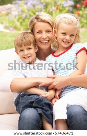 Mother And Children Relaxing In Garden - stock photo