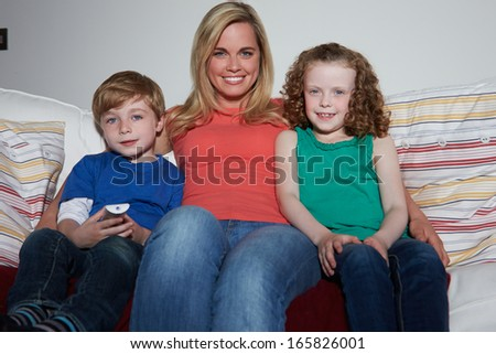 Mother And Children Sitting On Sofa Watching TV Together - stock photo