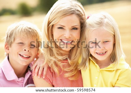 Mother And Children Sitting On Straw Bales In Harvested Field - stock photo