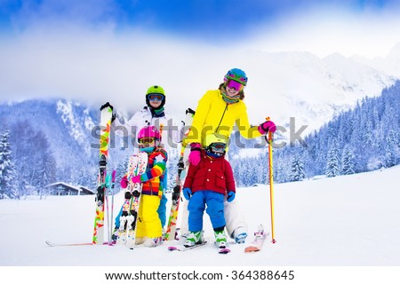 Mother and children skiing in the mountains. Active mom and three kids with safety helmet, goggles and poles. Ski lesson for young children. Winter sport and snow fun for family. Child learning to ski - stock photo