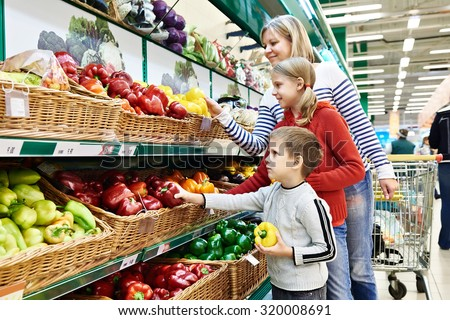 Mother and children with bell pepper in vegetables department in the supermarket - stock photo