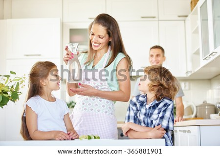 Mother and children with carafe water in the kitchen - stock photo