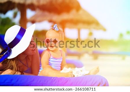 mother and cute little daughter having fun on summer tropical beach - stock photo