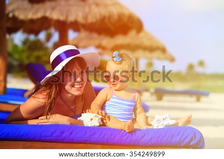 mother and cute little daughter having fun on summer tropical beach