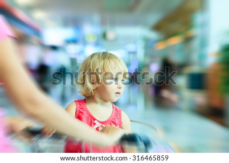 mother and cute little daughter on luggage cart in the airport, family travel - stock photo