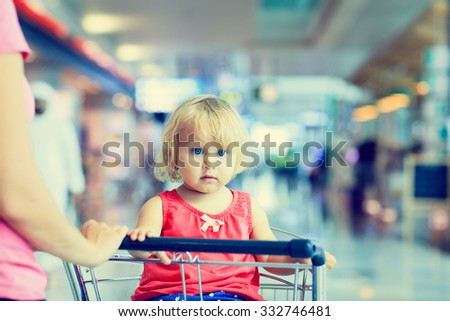 mother and cute little daughter on luggage cart in the airport, family travel