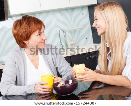 Mother and daudhter talking on the kitchen. Women at home