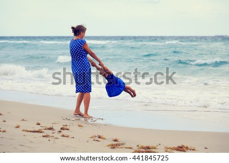 mother and daugher playing on beach - stock photo