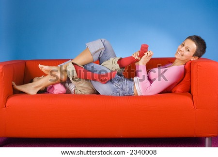 mother and daughet tickling each other on the red sofa - stock photo